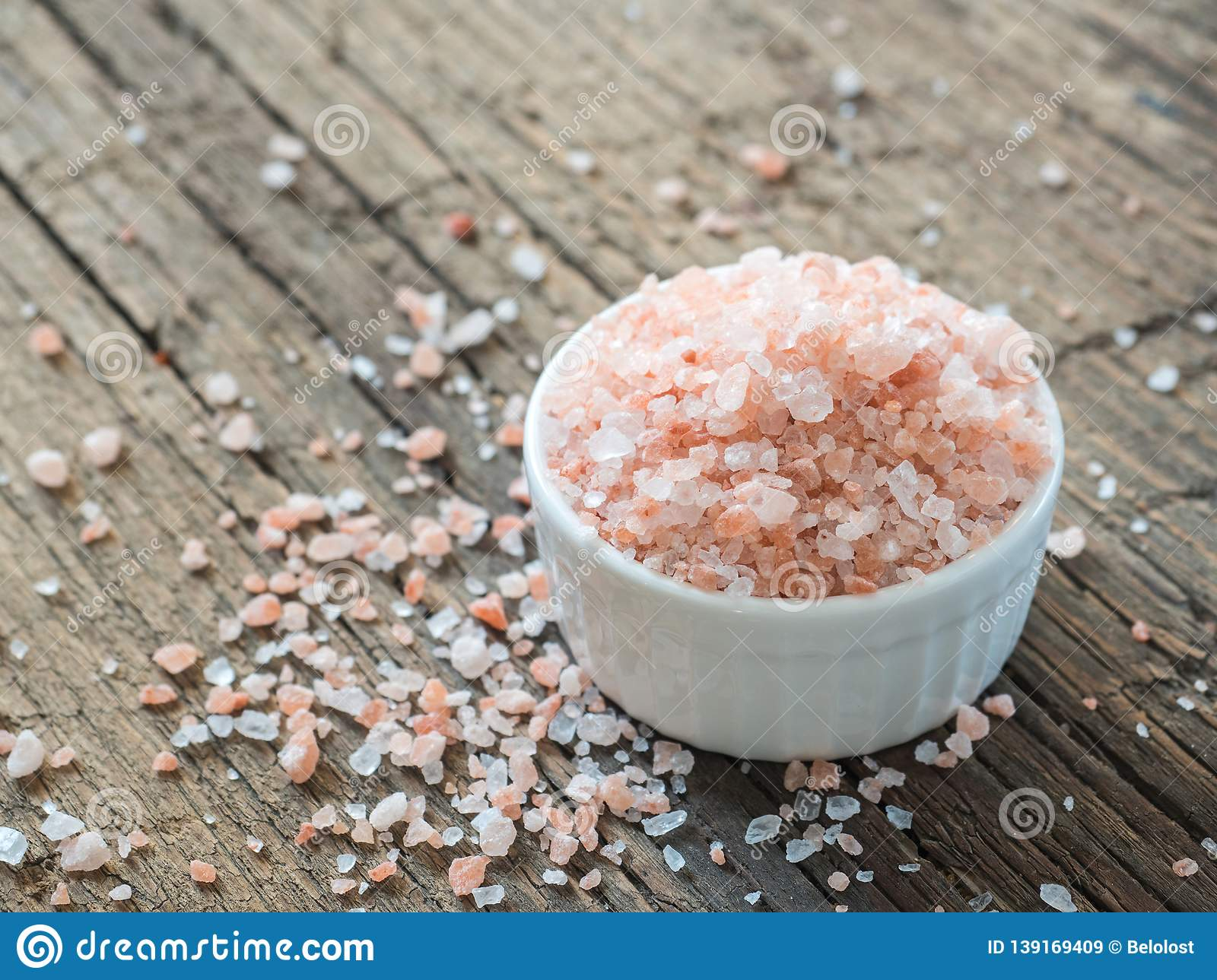 Pink Himalayan salt in white salt shaker on wooden background. Healthy spice closeup