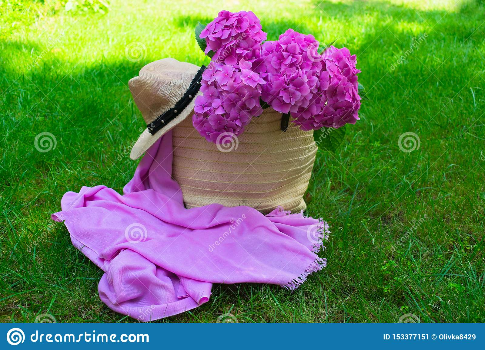 Pink hydrangea flowers in a wicker women`s summer bag and a sun hat on lush green grass.