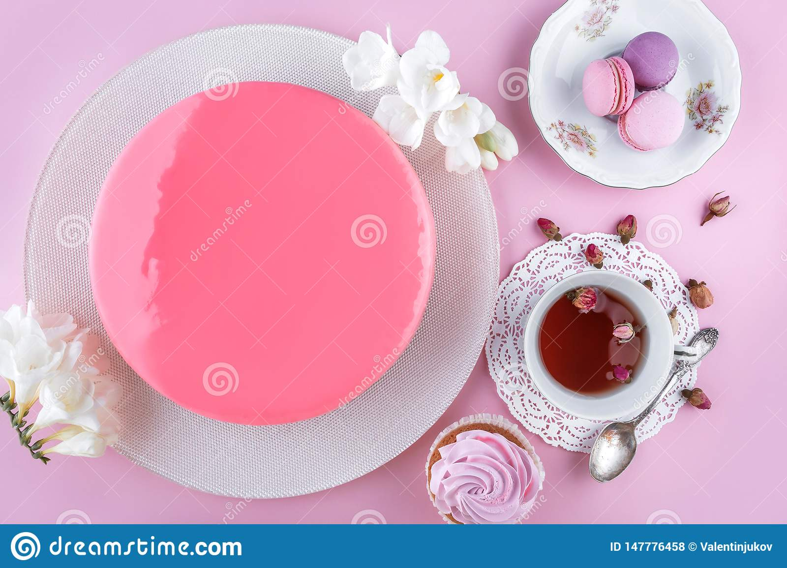 Pink mousse cake with mirror glaze decorated with macaroons, flowers for Happy Birthday on pink holiday background. Holiday cake