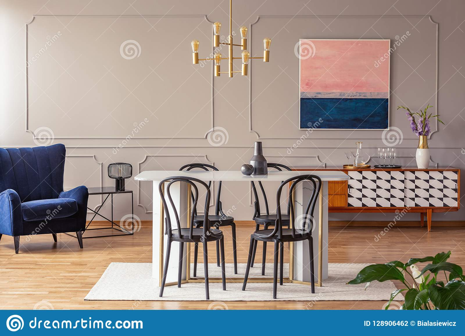 Pink and navy blue abstract painting on a gray wall with molding in an elegant dining and living room