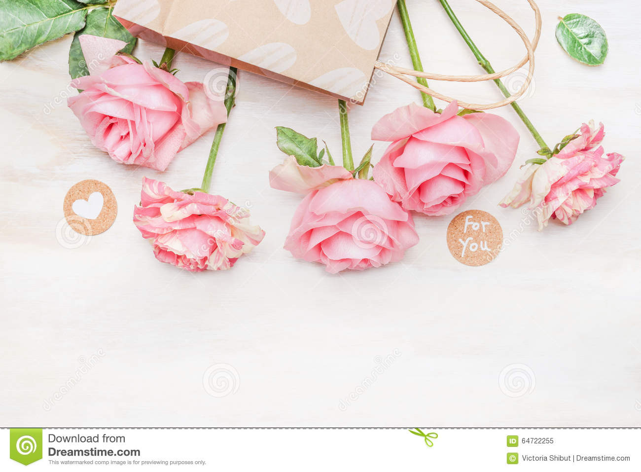 Pink pale roses paper shopping bag and round sign with message for you and heart on white wooden background, top view