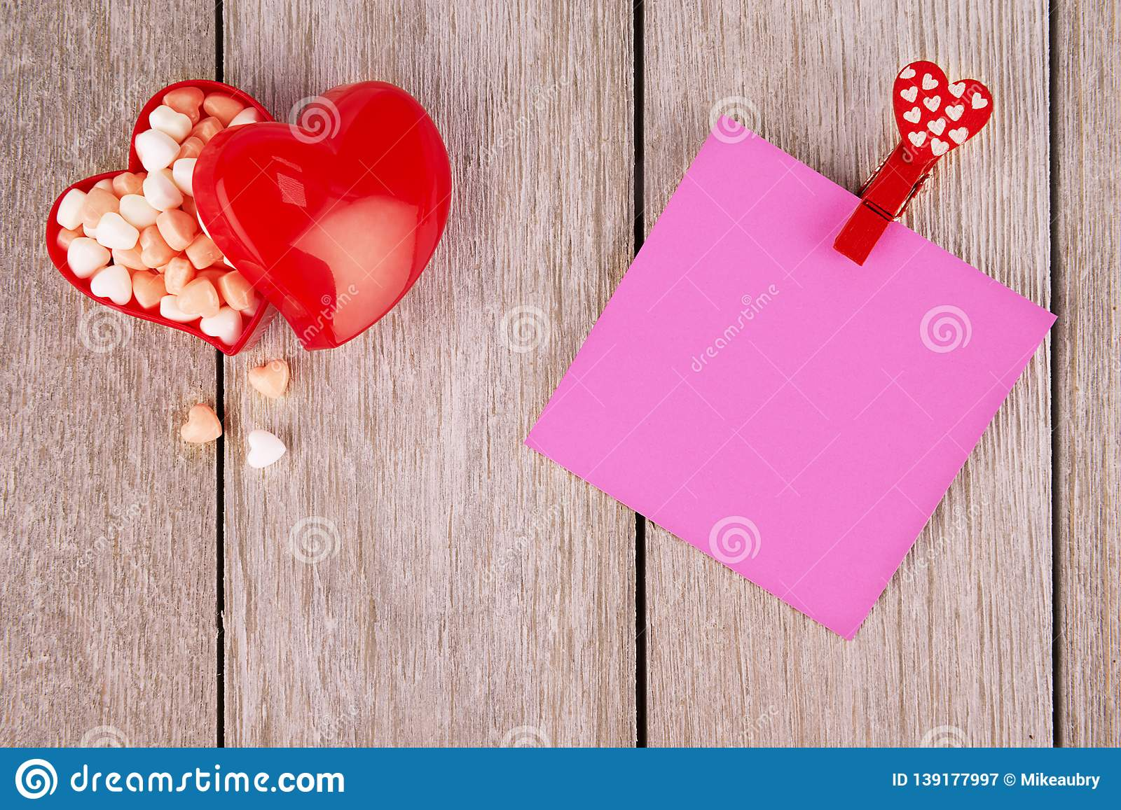 Pink paper notepad on white wooden plank in background.