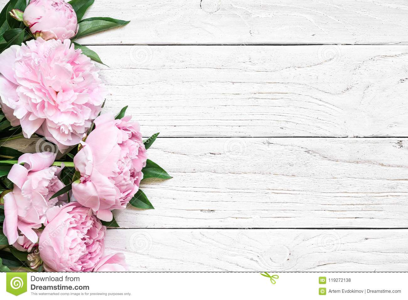 Pink peony flowers over white wooden table with copy space. wedding invitation. flat lay