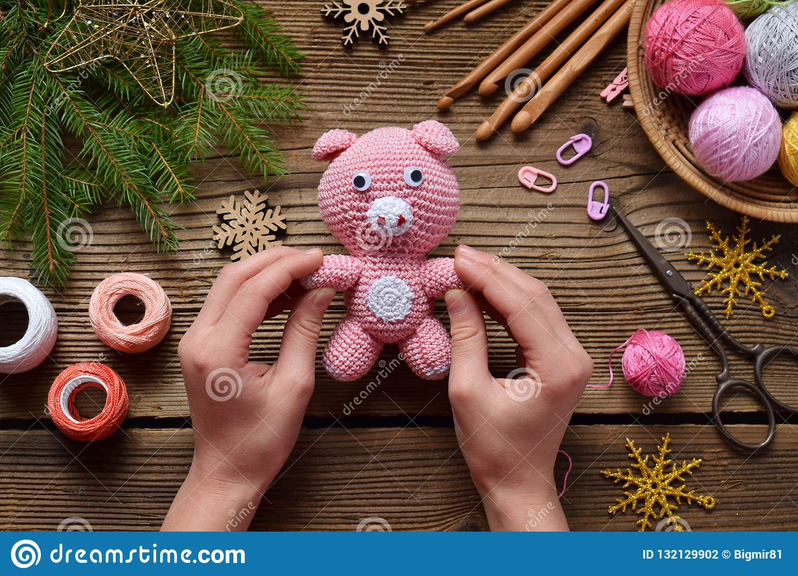 Pink pig, symbol of 2019. Happy New Year. Crochet toy for child. On table threads, needles, hook, cotton yarn. Handmade crafts on