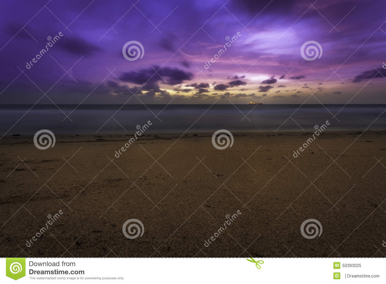 pink and purple beach sunrise with ship on horizon stock