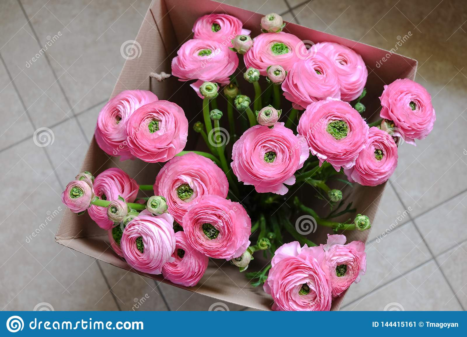 Pink Ranunculus bouquet in a cardboard box on the floor. Top view. For flower delivery, social media. Soft selective focus.