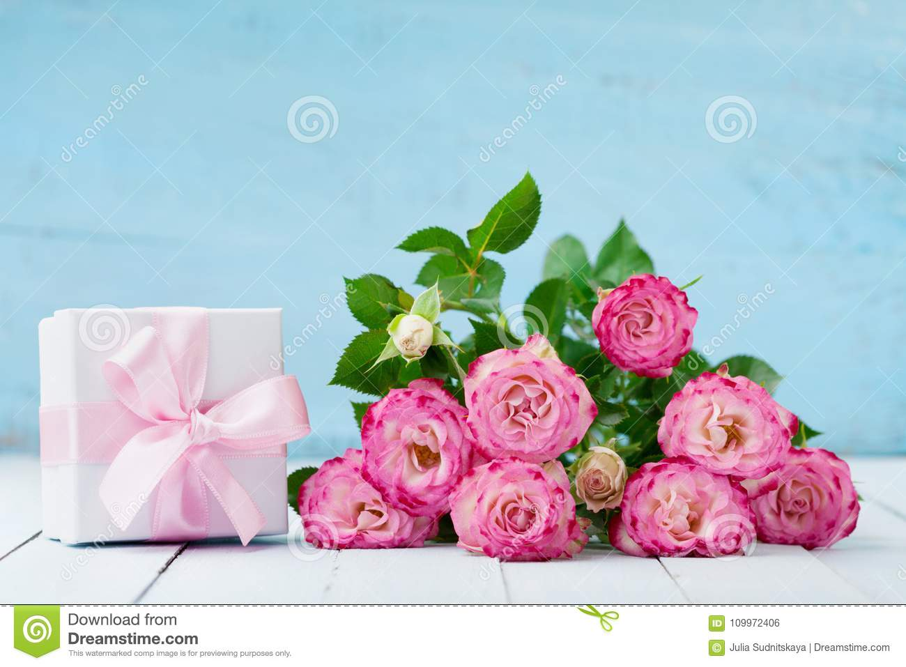 Pink Rose Flower Bouquet And Gift Box With Ribbon On Blue Table