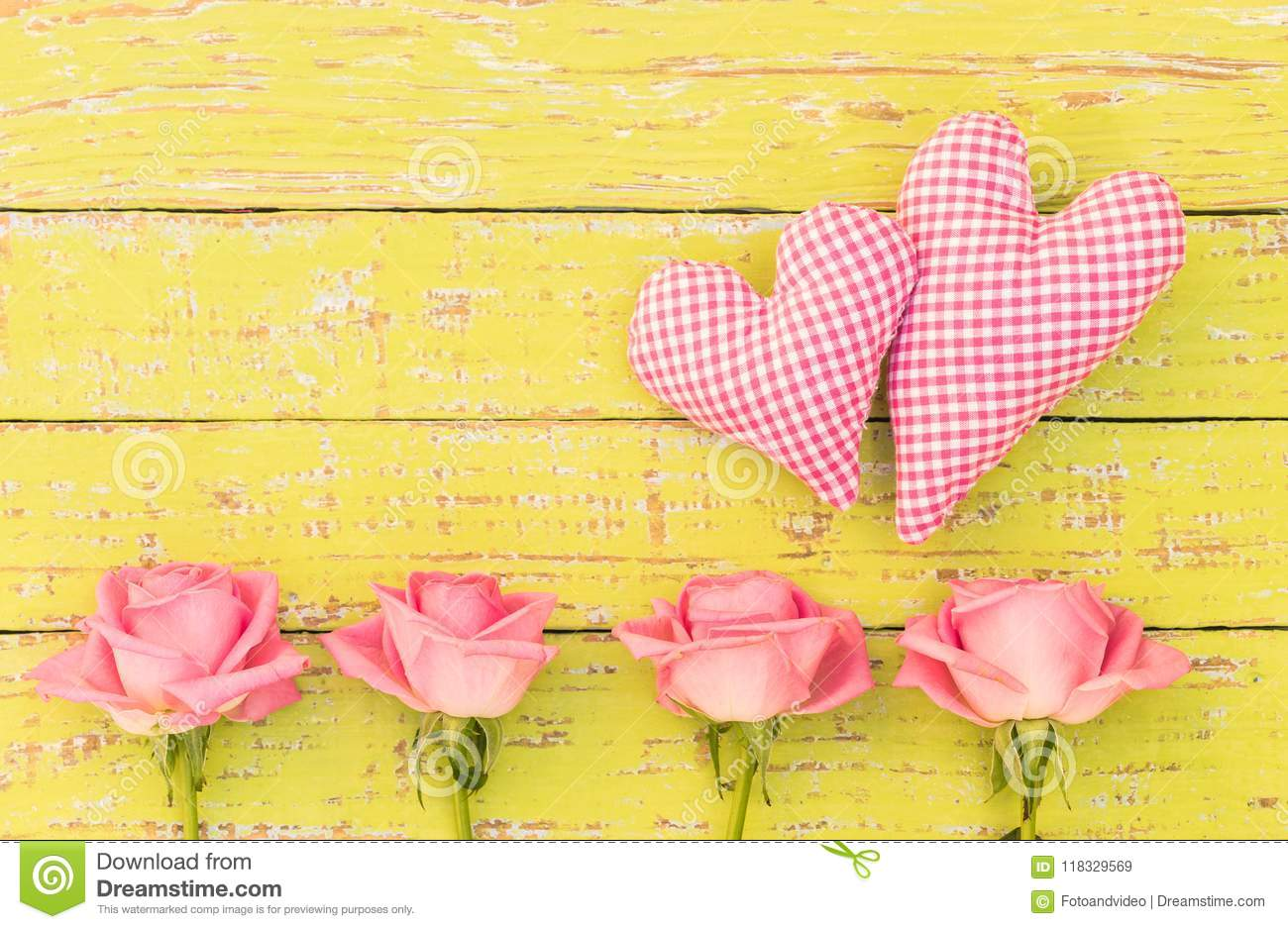 Pink roses flower arrangement with two hearts on yellow wooden background with copy space
