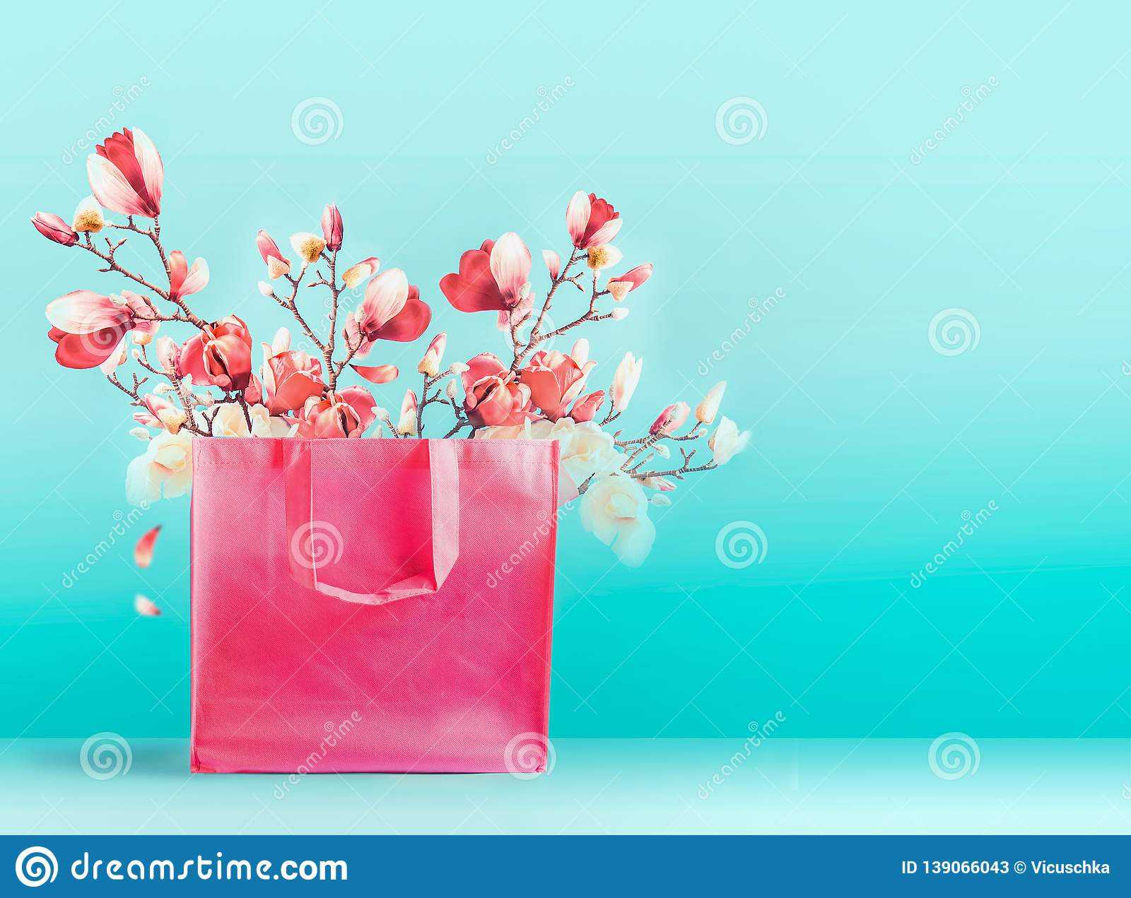Pink shopping bag with spring blossom branches standing at turquoise blue background. Trendy color. Creative spring time and