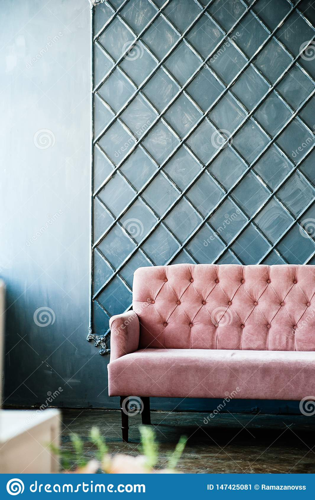 Pink sofa on blue wall background, place for inscription