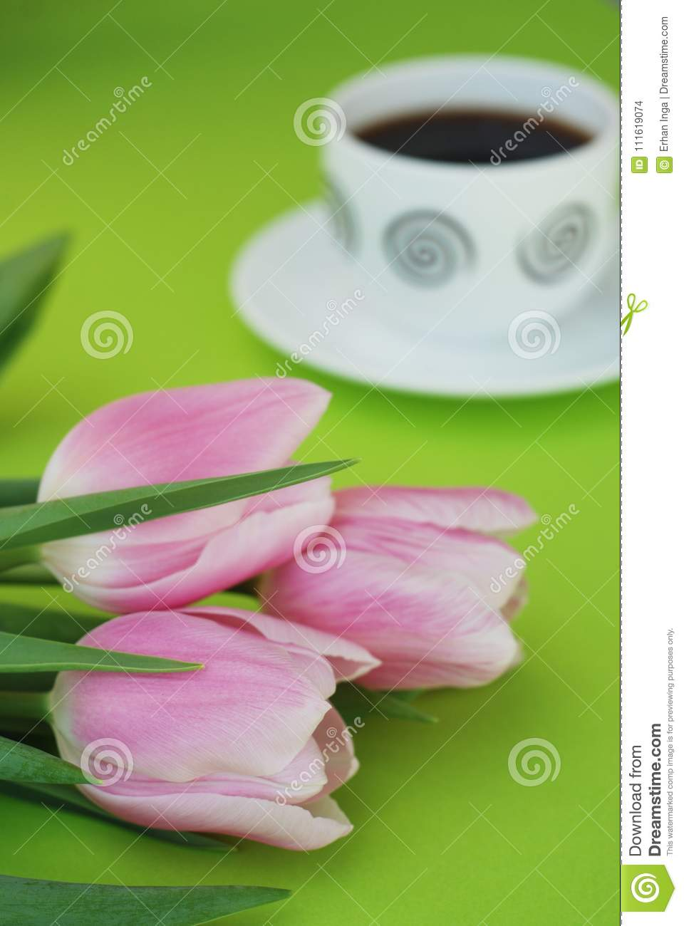 Pink Spring Tulips over a Green background, in a flat lay composition with Copy space. Spring flowers with Cup of cofee.