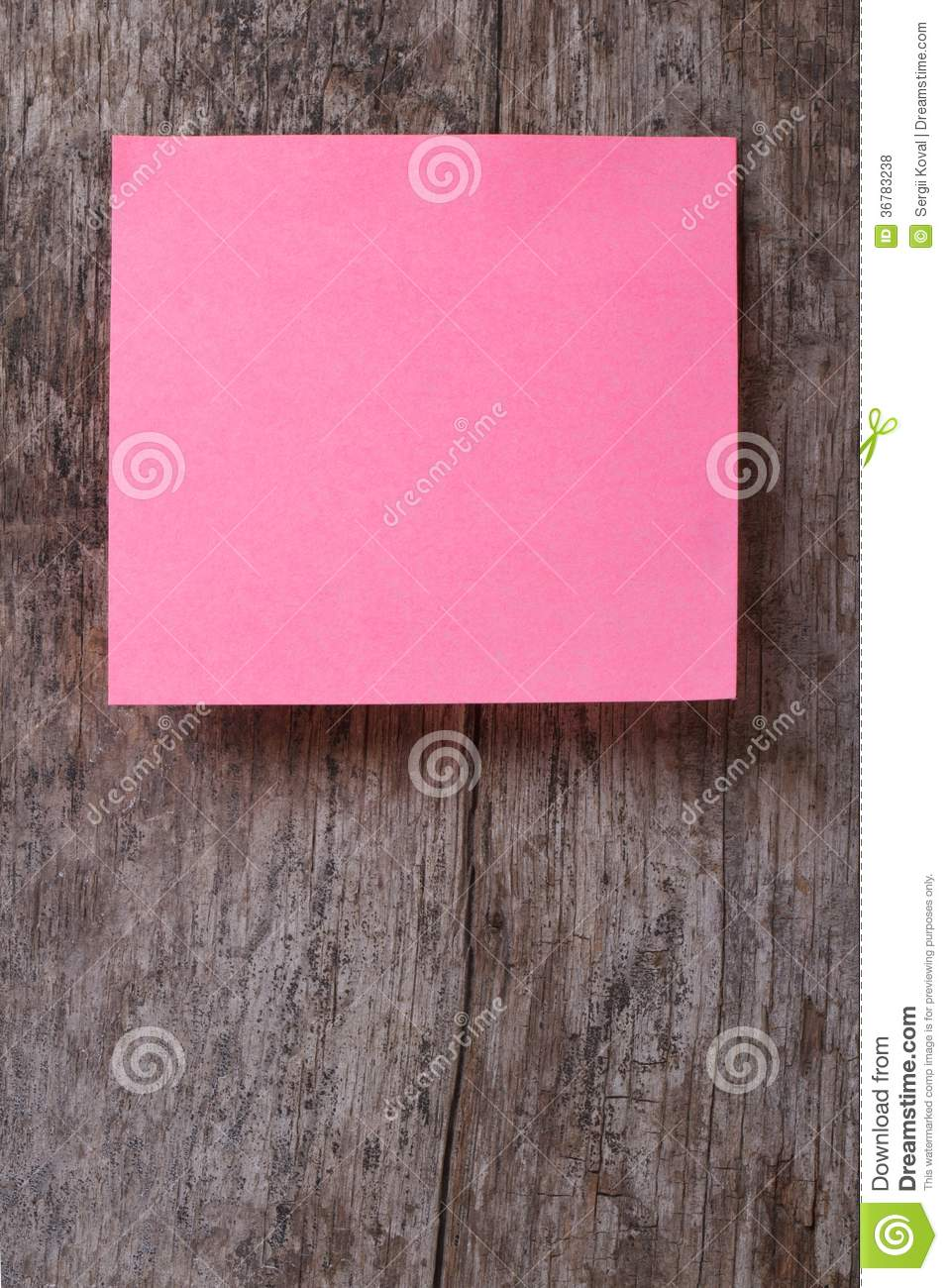 Pink sticker on an old wooden table close up royalty free