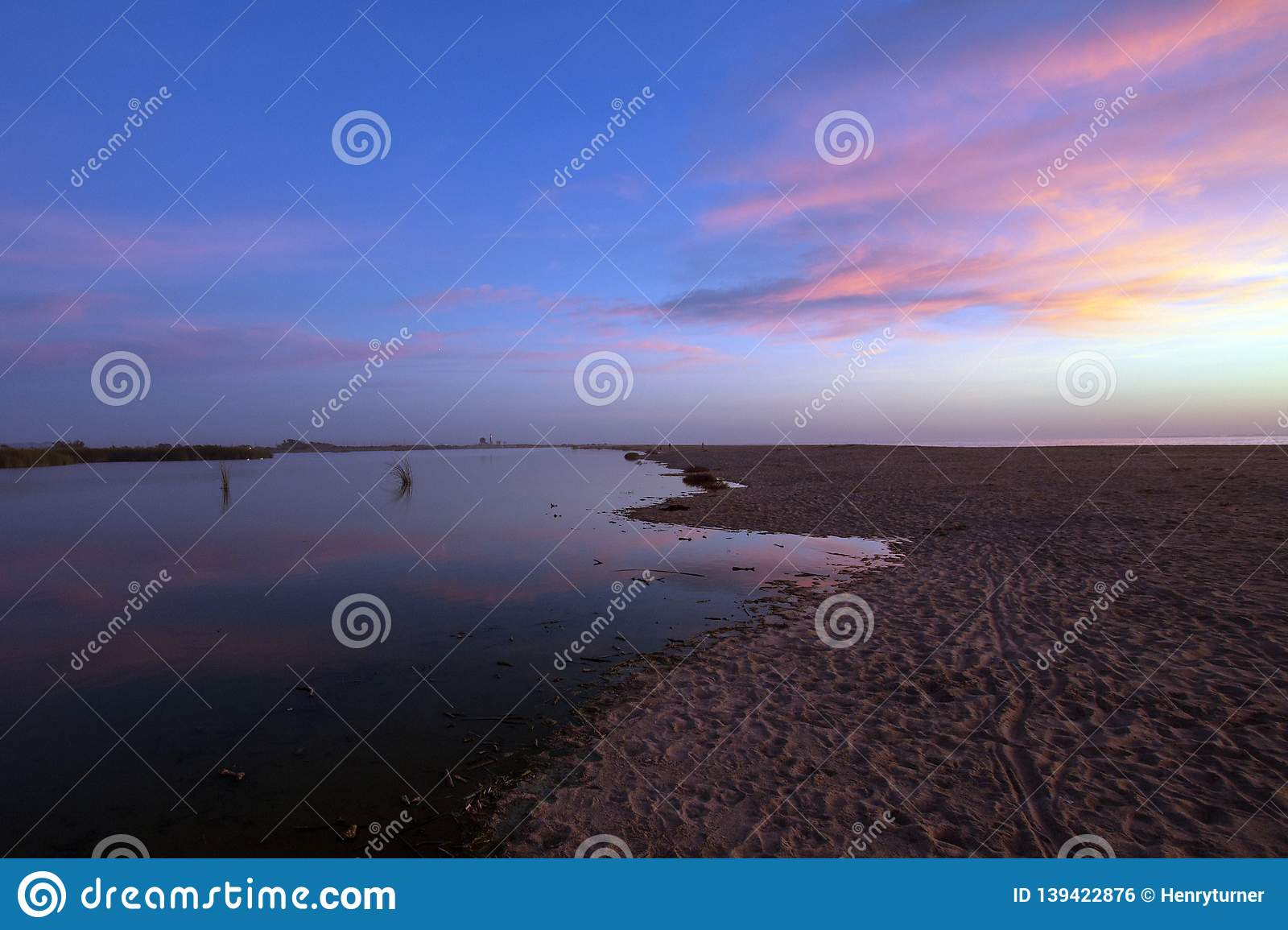 Pink sunset cloud reflection over Santa Clara river seaside marsh at Ventura beach in California USA