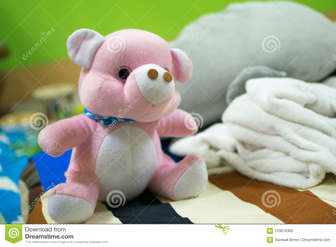 Pink teddy bear placed on the bed.