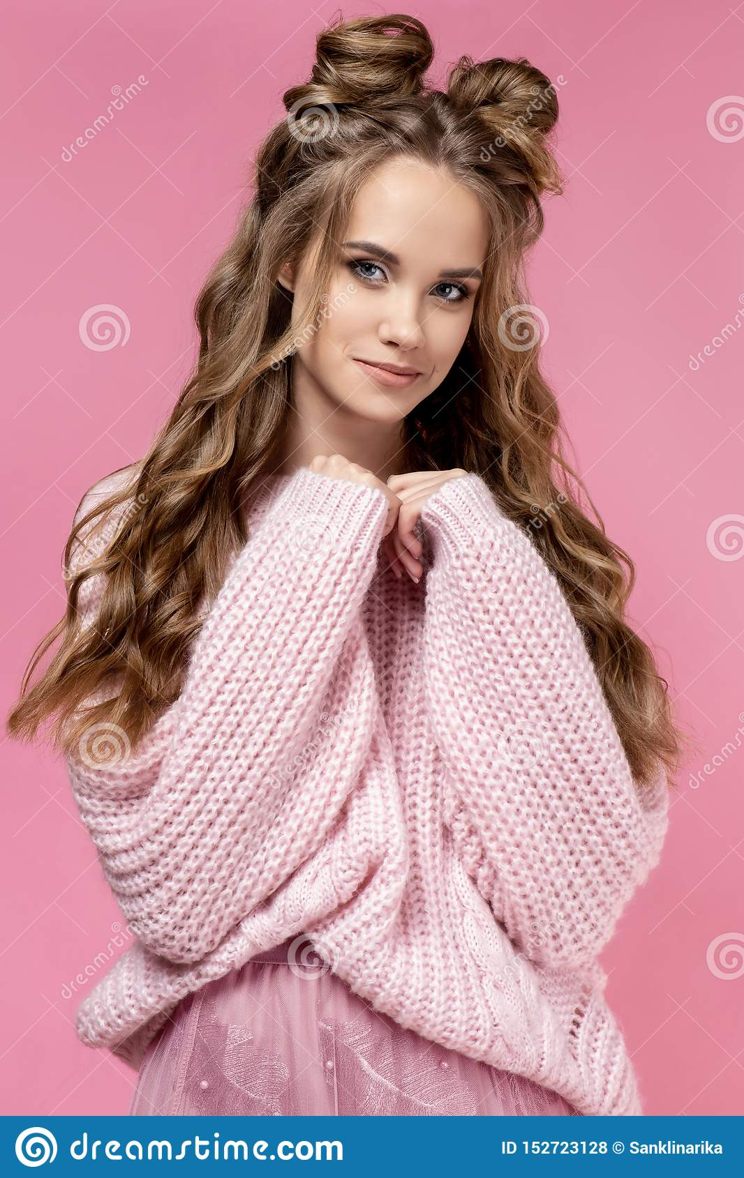 Pretty young girl in a pink sweater on a pink background with a haircut and curly long hair.