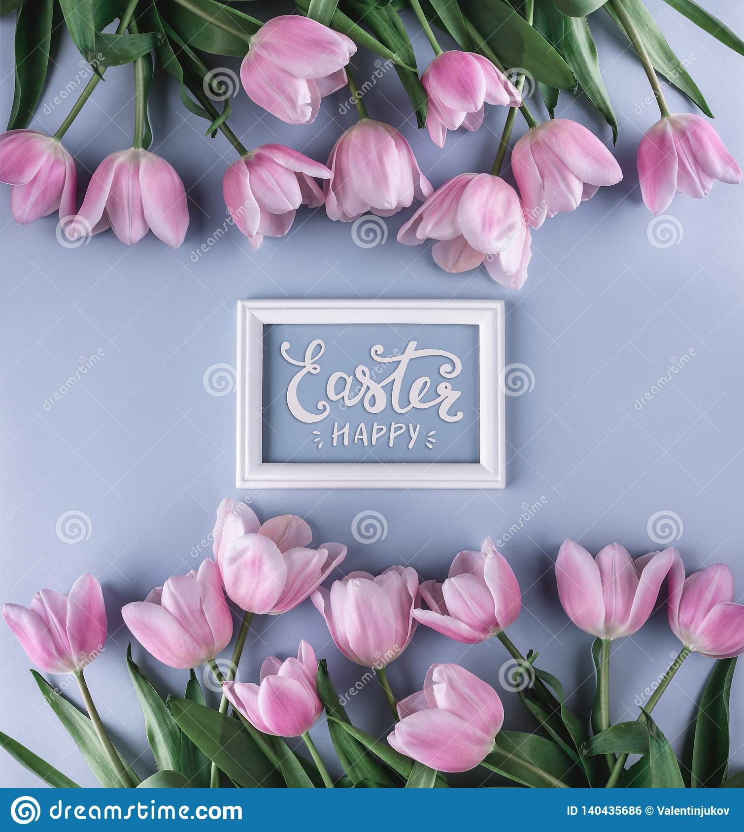 Pink tulips flowers on blue background with frame for text. Waiting for spring. Happy Easter card. Flat lay, top view