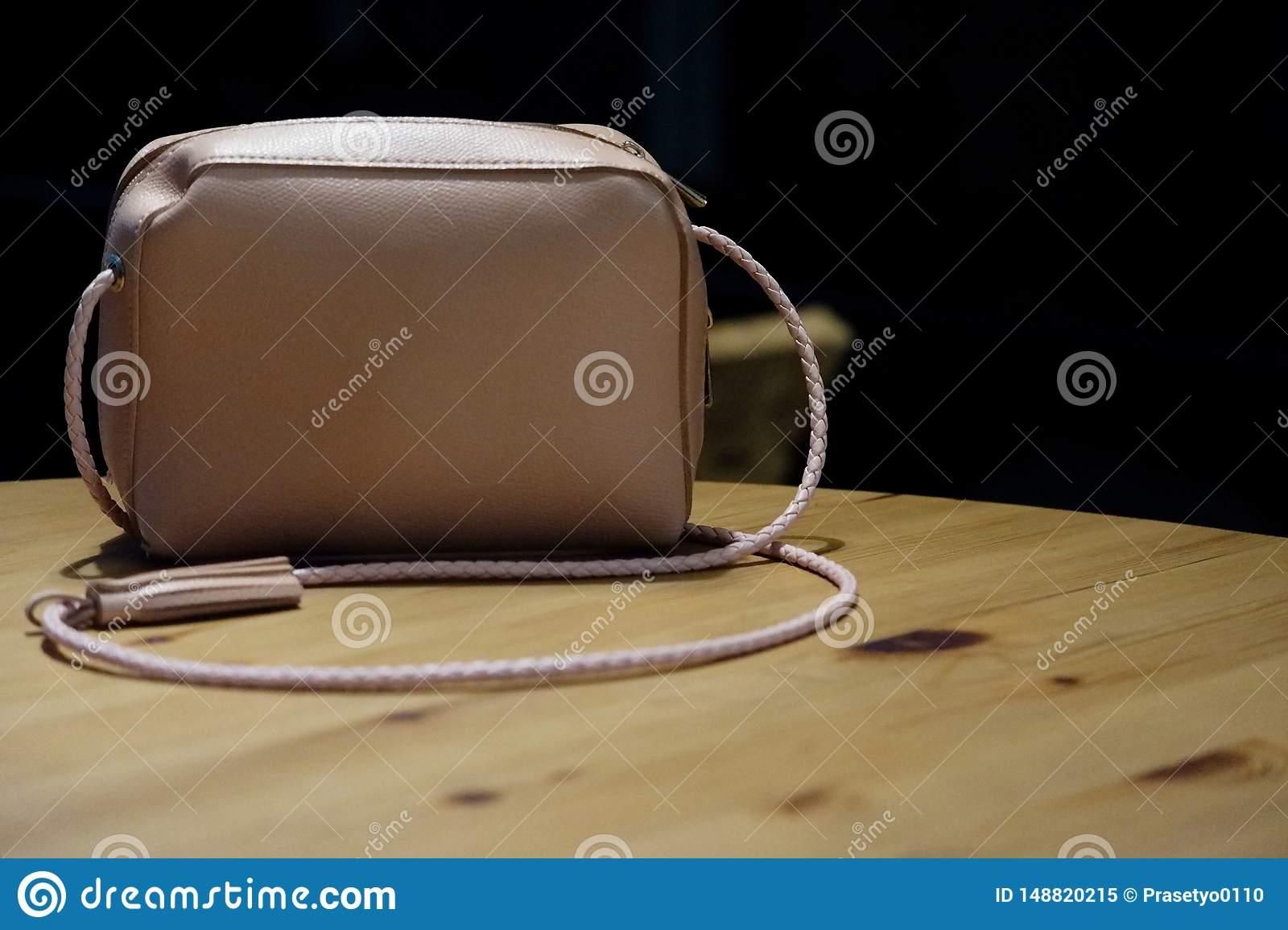 Pink woman bag on the wooden table.