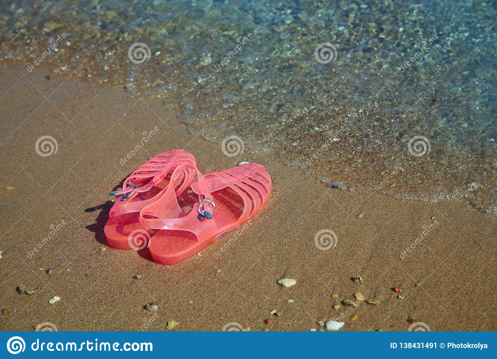 a4d328acb7e Pink Women`s JELLY SANDALS on a sea shore. LADIES FLAT JELLIES SUMMER BEACH  SHOES. Sand background