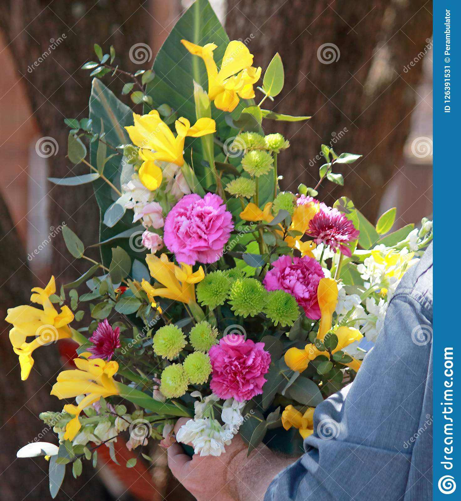 Pink And Yellow Flower Arrangement Held By A Person Stock Image