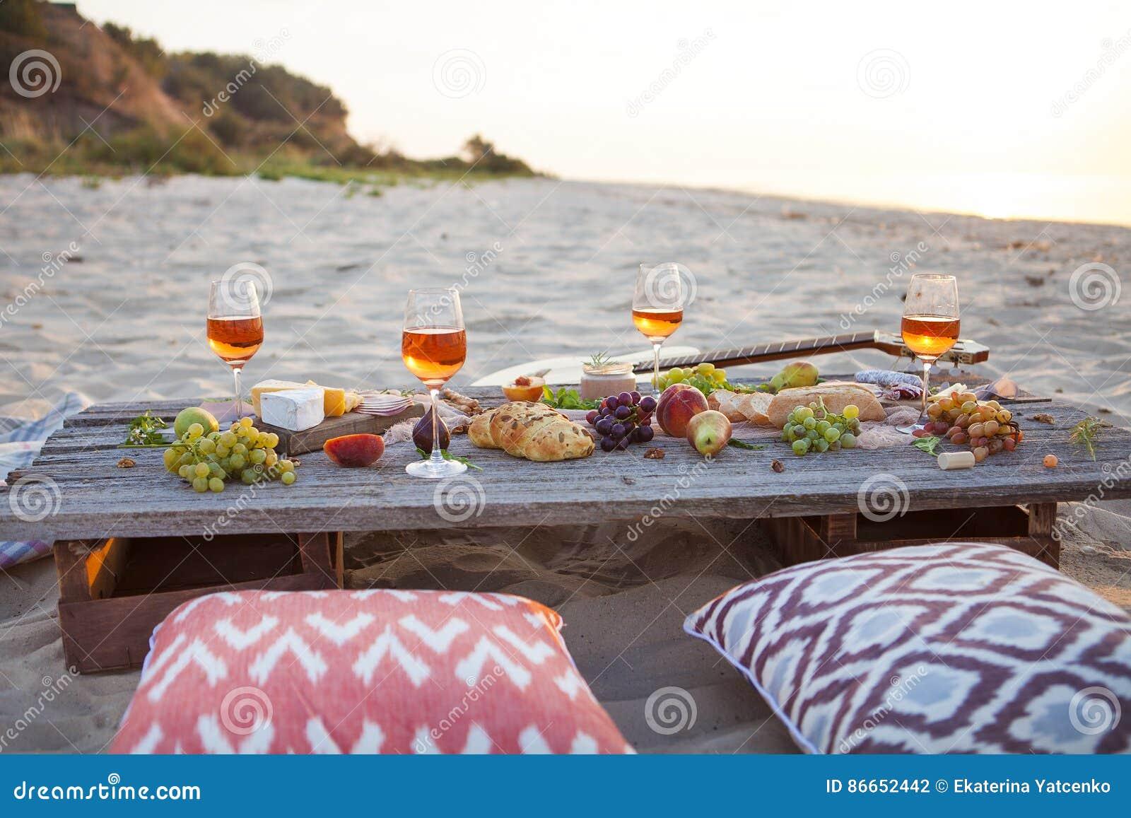 Pinkin na plaży przy zmierzchem w boho stylu, jedzeniu i napoju conc,