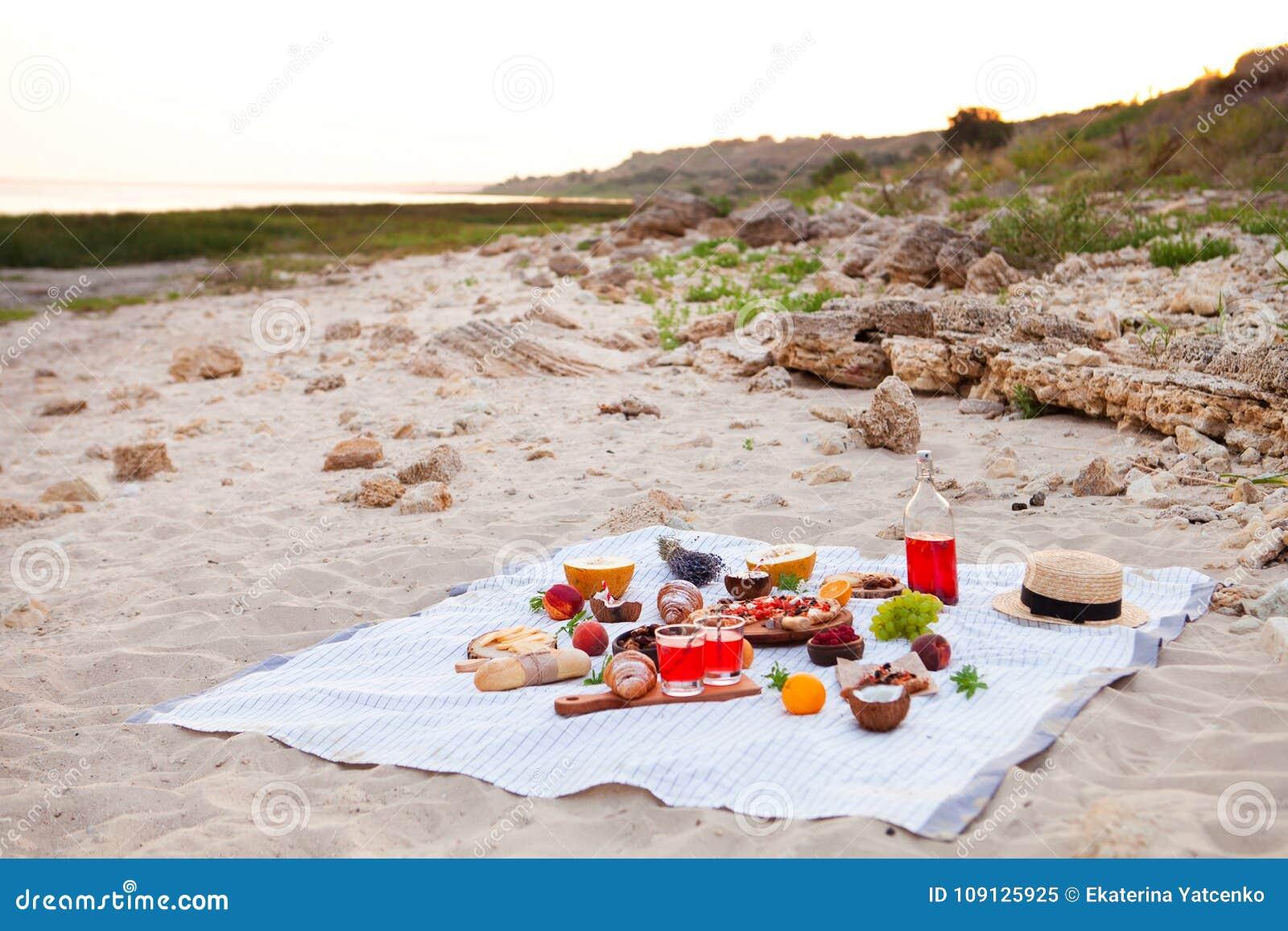 Pinkin na plaży przy zmierzchem w szkockiej kracie, jedzeniu i napoju białych,