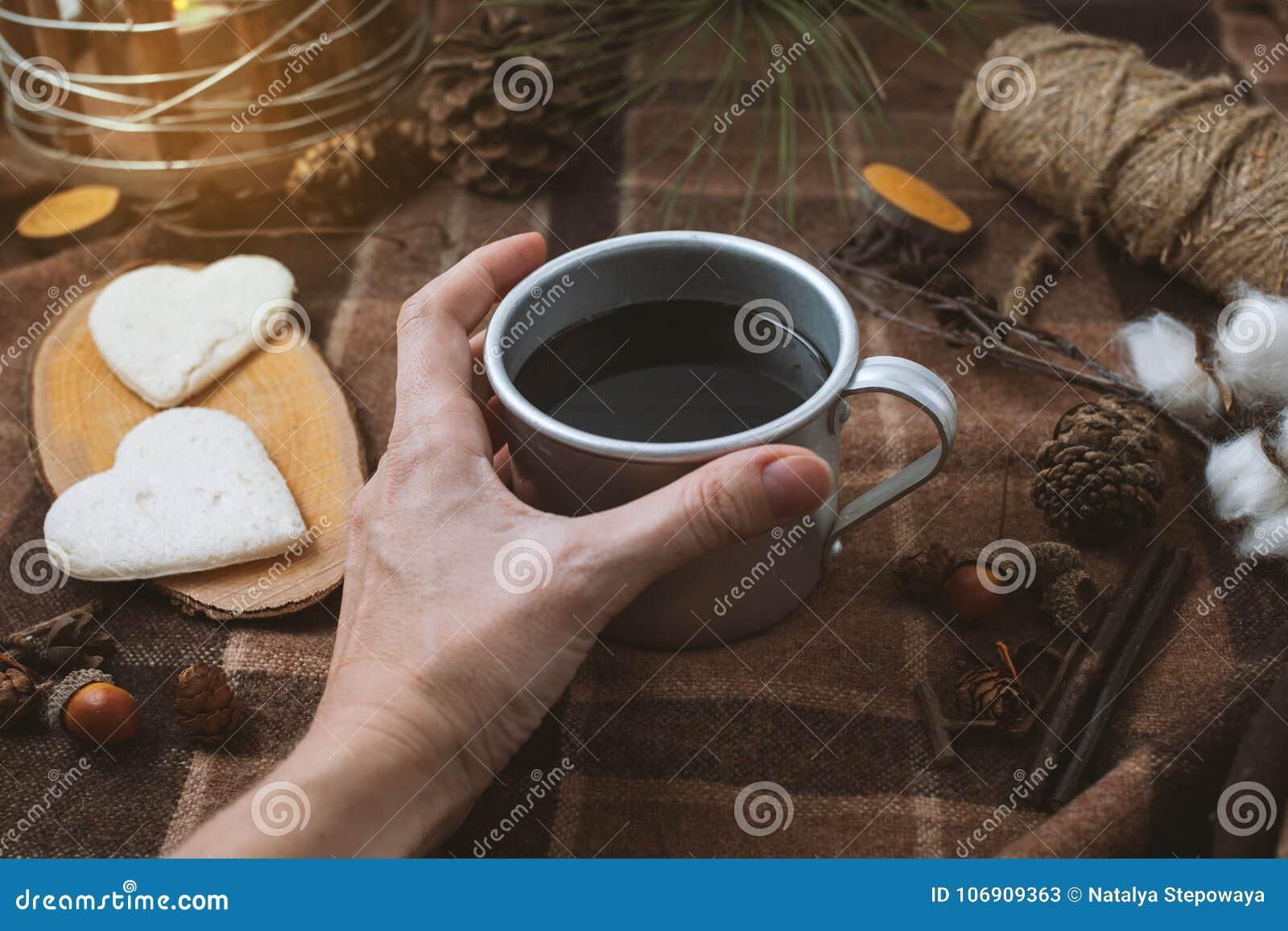 Pinkin w naturze, rękach trzyma filiżankę czarna kawa, szkockiej kracie i sercach,