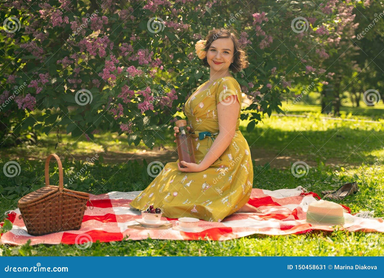 Pino novo bonito acima da menina que tem o resto na natureza vestido vestindo do vintage da jovem mulher magro feliz que senta-se