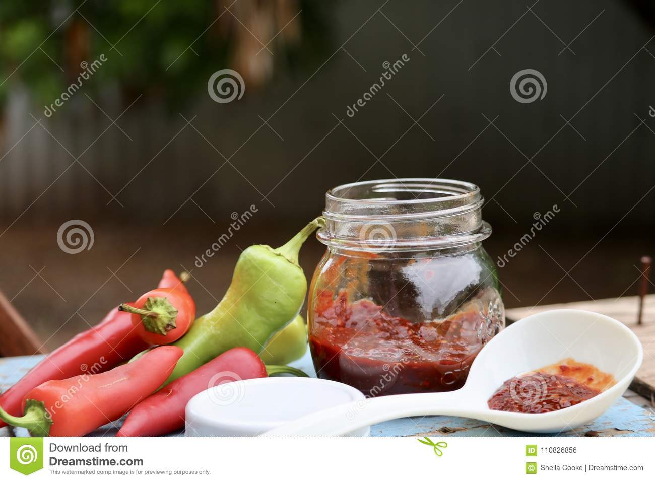Pint glass jar of homemade red and green Chile pepper sauce