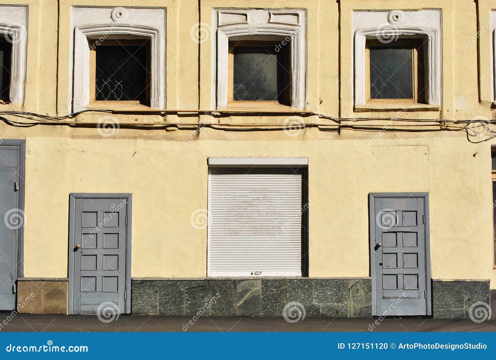 Pintado na parede amarela da construção com as janelas e as portas ascendentes embarcadas
