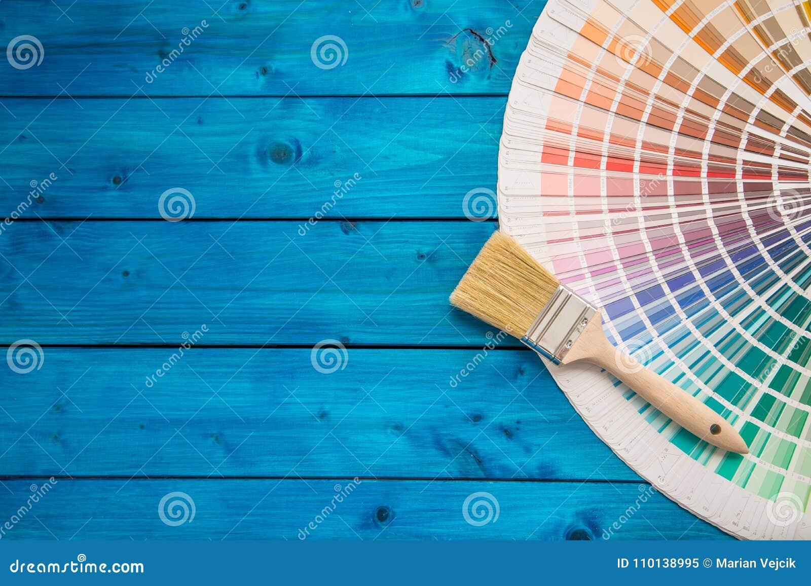 Pinte latas paleta de cores, latas abertas com as escovas na tabela azul