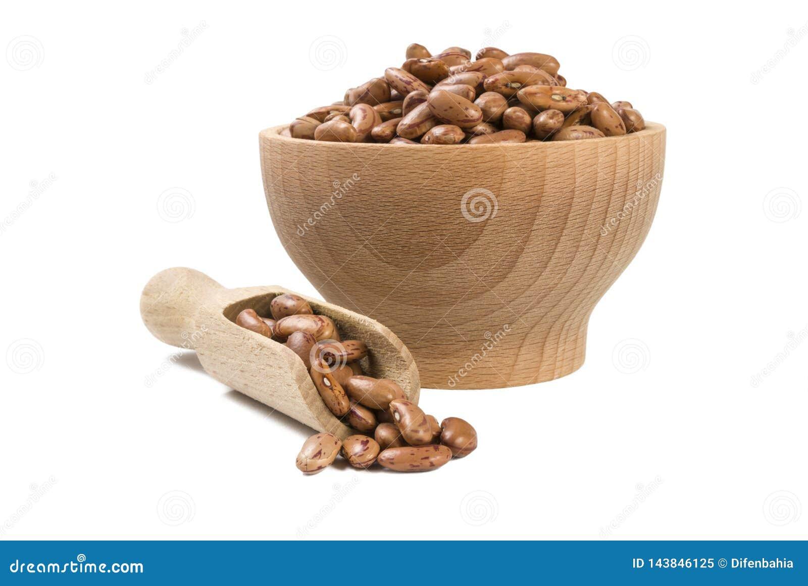 Pinto φασόλι στο ξύλινο κύπελλο και σέσουλα που απομονώνεται στο άσπρο υπόβαθρο διατροφή βιο Φυσικό συστατικό τροφίμων