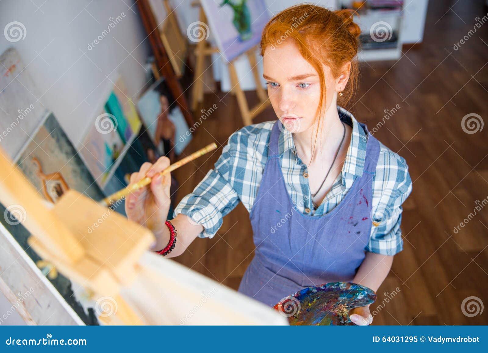 Pintor concentrado de la mujer que sostiene la paleta del arte y que la pinta en lona