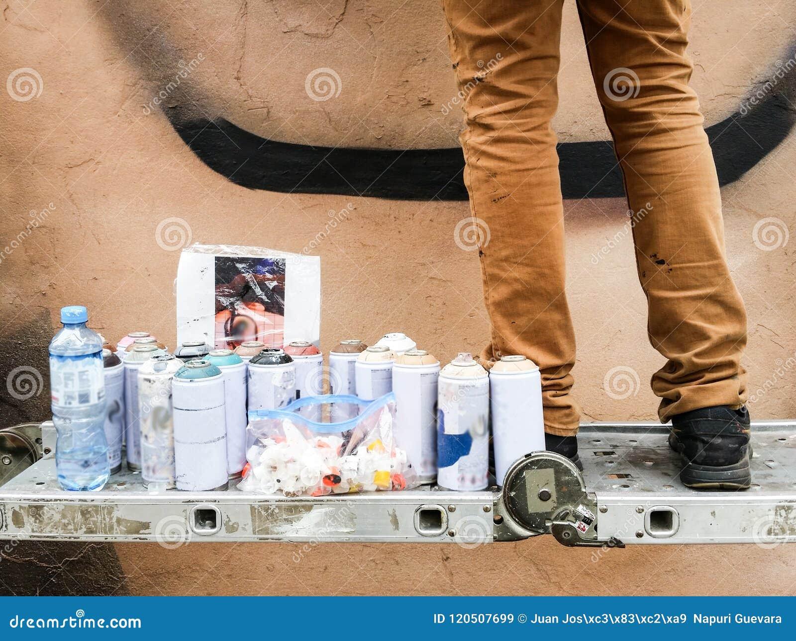 Pintor urbano joven que comienza a dibujar la pintada en la pared en la calle
