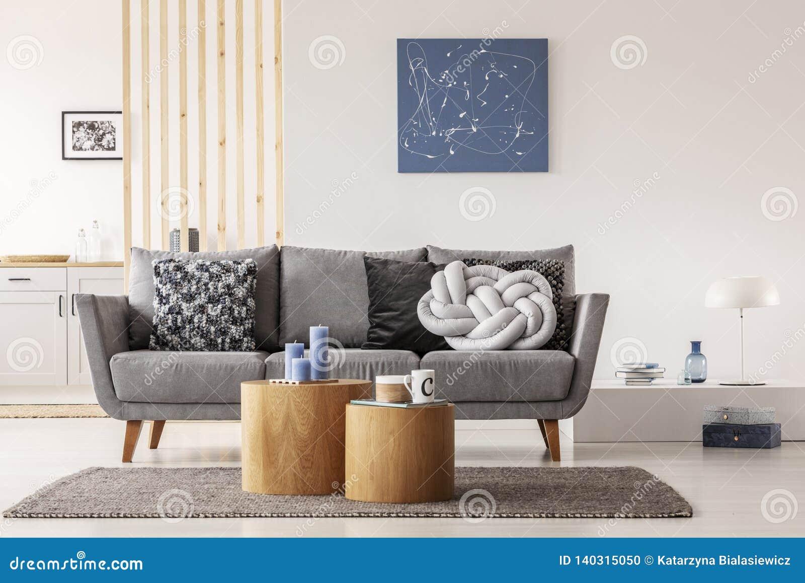 Pintura abstrata azul na parede branca da sala de visitas contemporânea interior com o canapé cinzento com descansos
