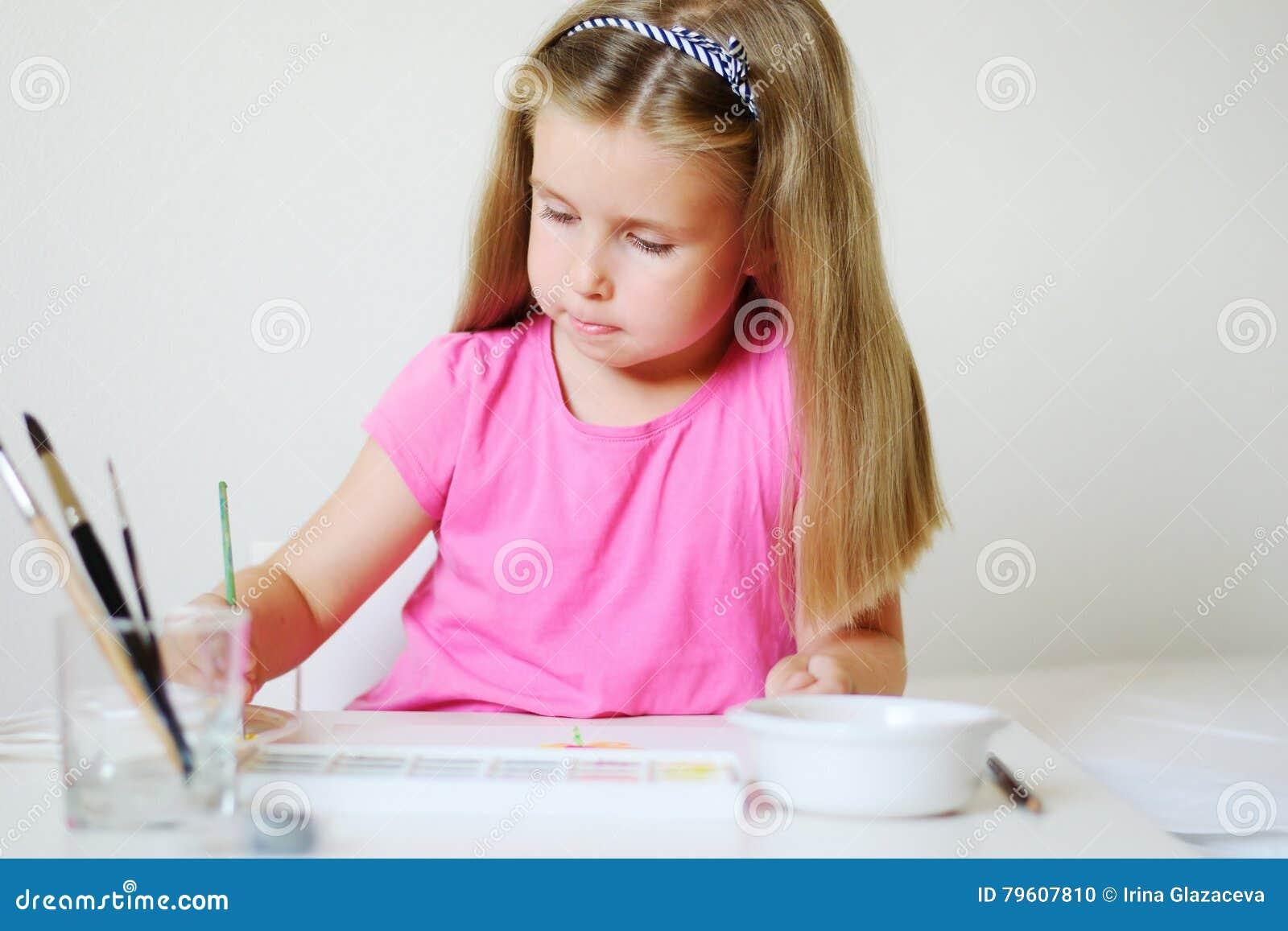 Pintura adorável da menina com aquarela em uma sala branca ensolarada em casa