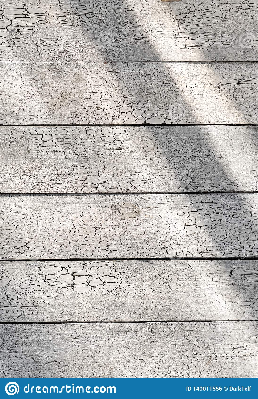 Pintura agrietada en tablones rústicos lamentables del fondo de madera blanco con luz del sol