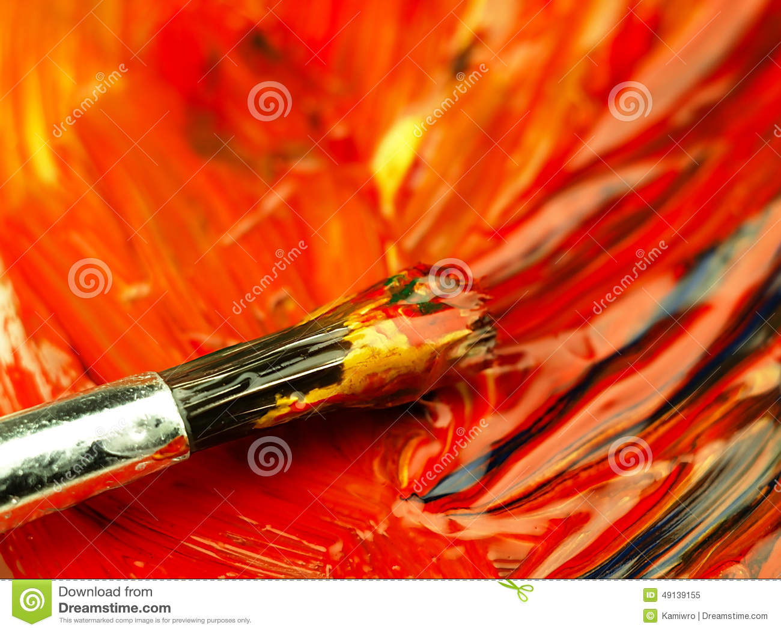 Pintura colorida misturada na paleta Escova suja no primeiro plano