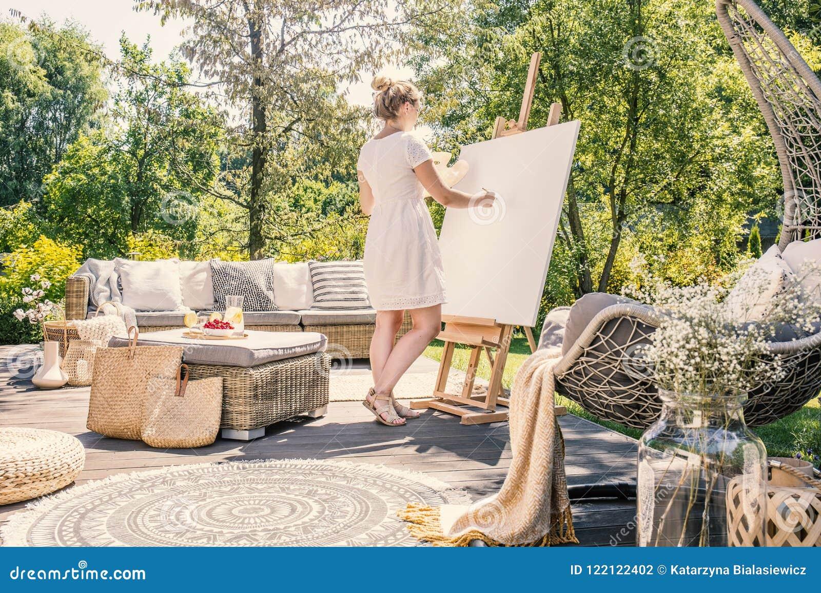 Pintura da jovem mulher em uma lona branca em um terraço ensolarado com g