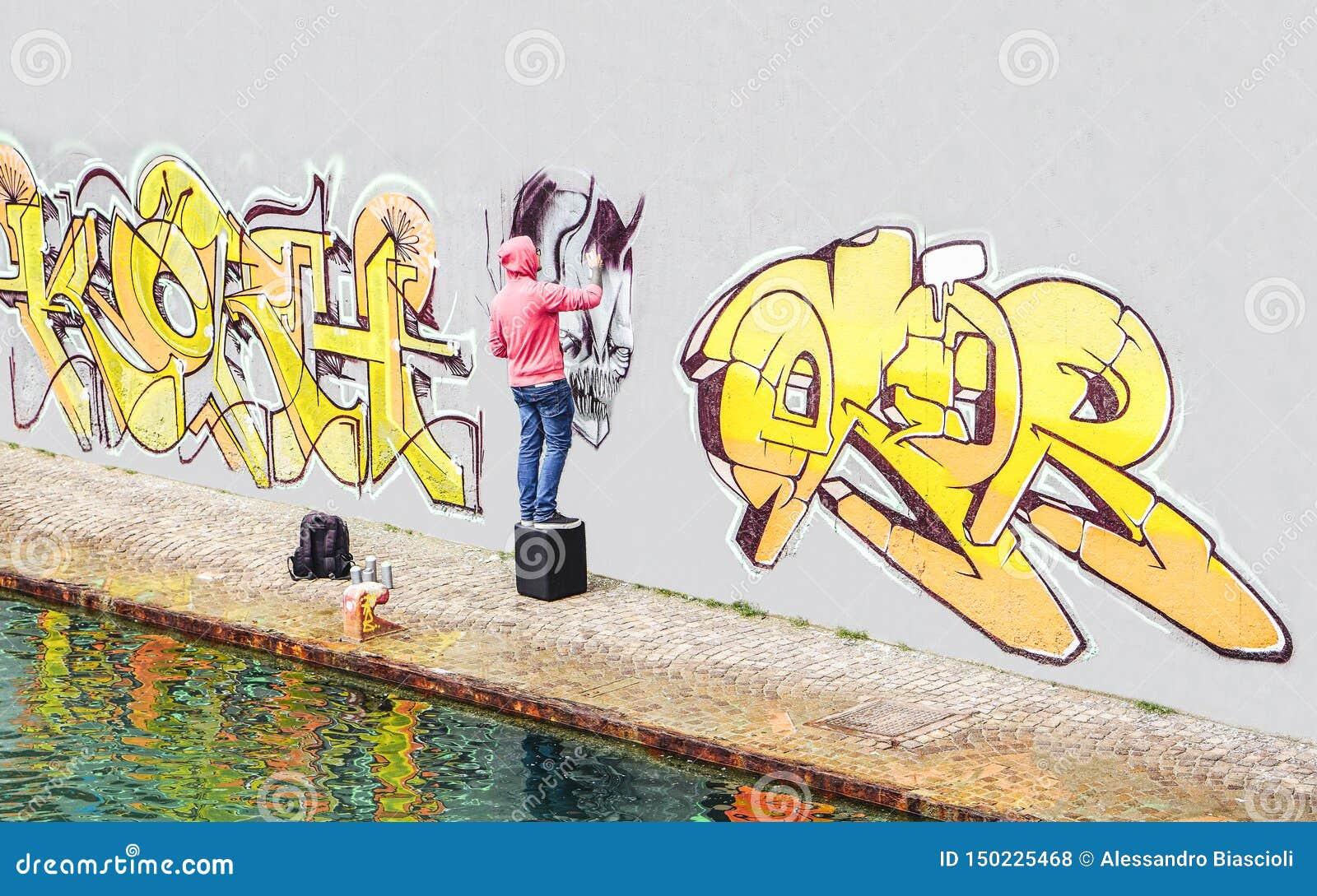 Pintura do artista dos grafittis da rua com uma lata de pulverizador da cor um grafitti na parede na cidade - conceito do estilo