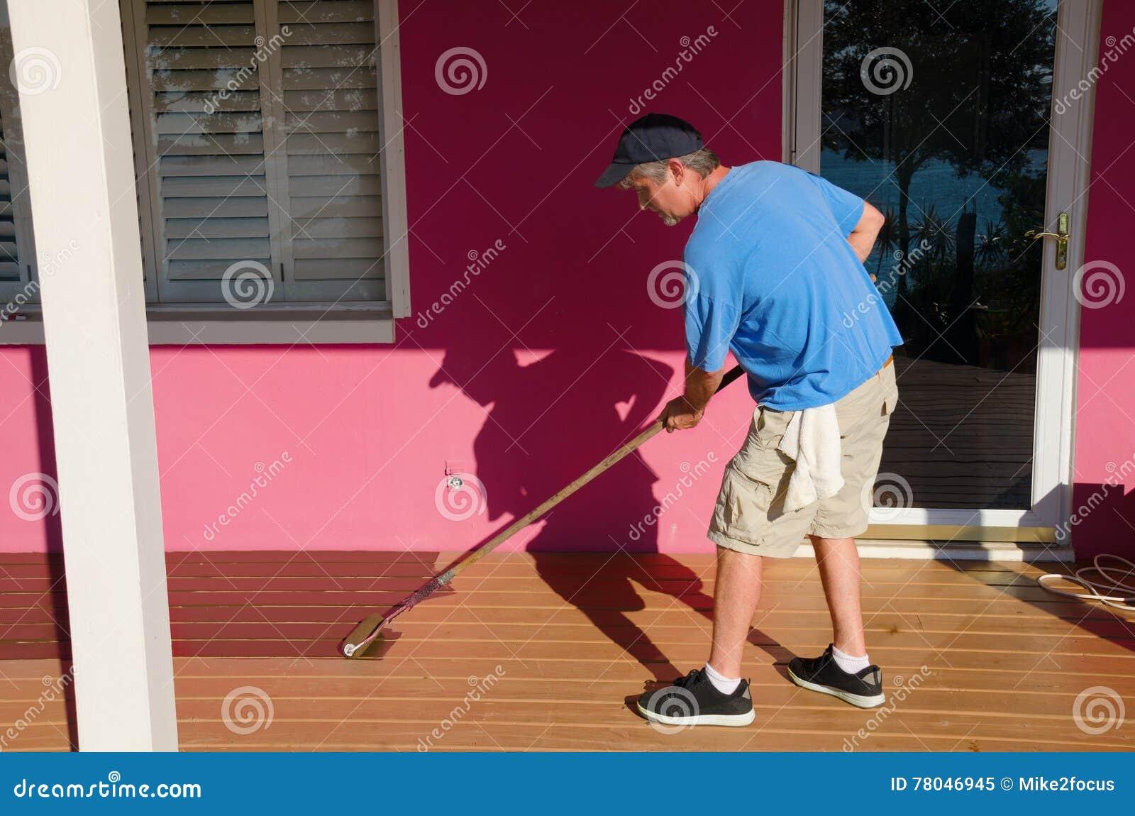 Pintura do proprietário de casa de DIY que mancha a plataforma de madeira