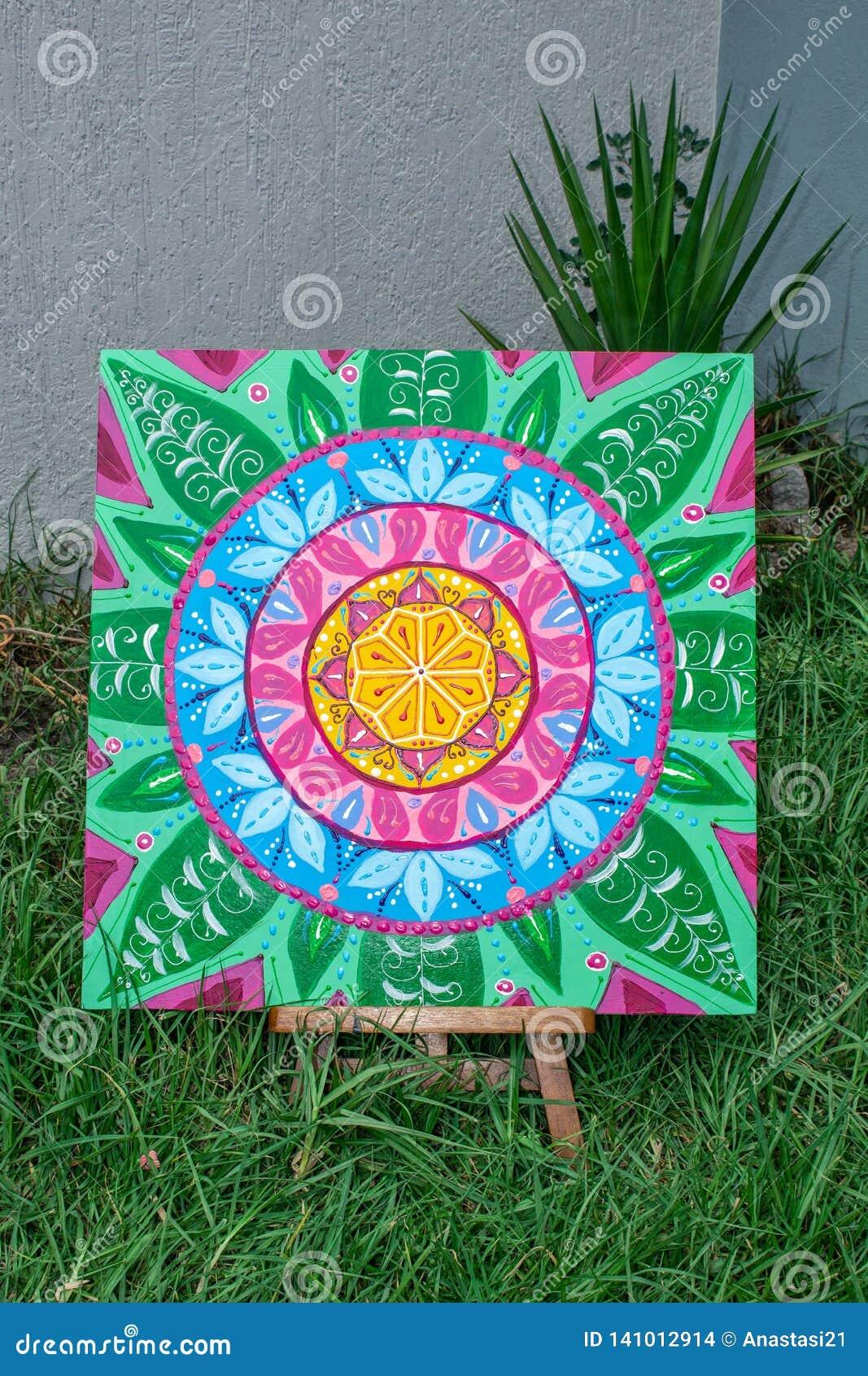 Pintura, pintando una situación de la mandala en un caballete, al aire libre en la hierba, colores brillantes