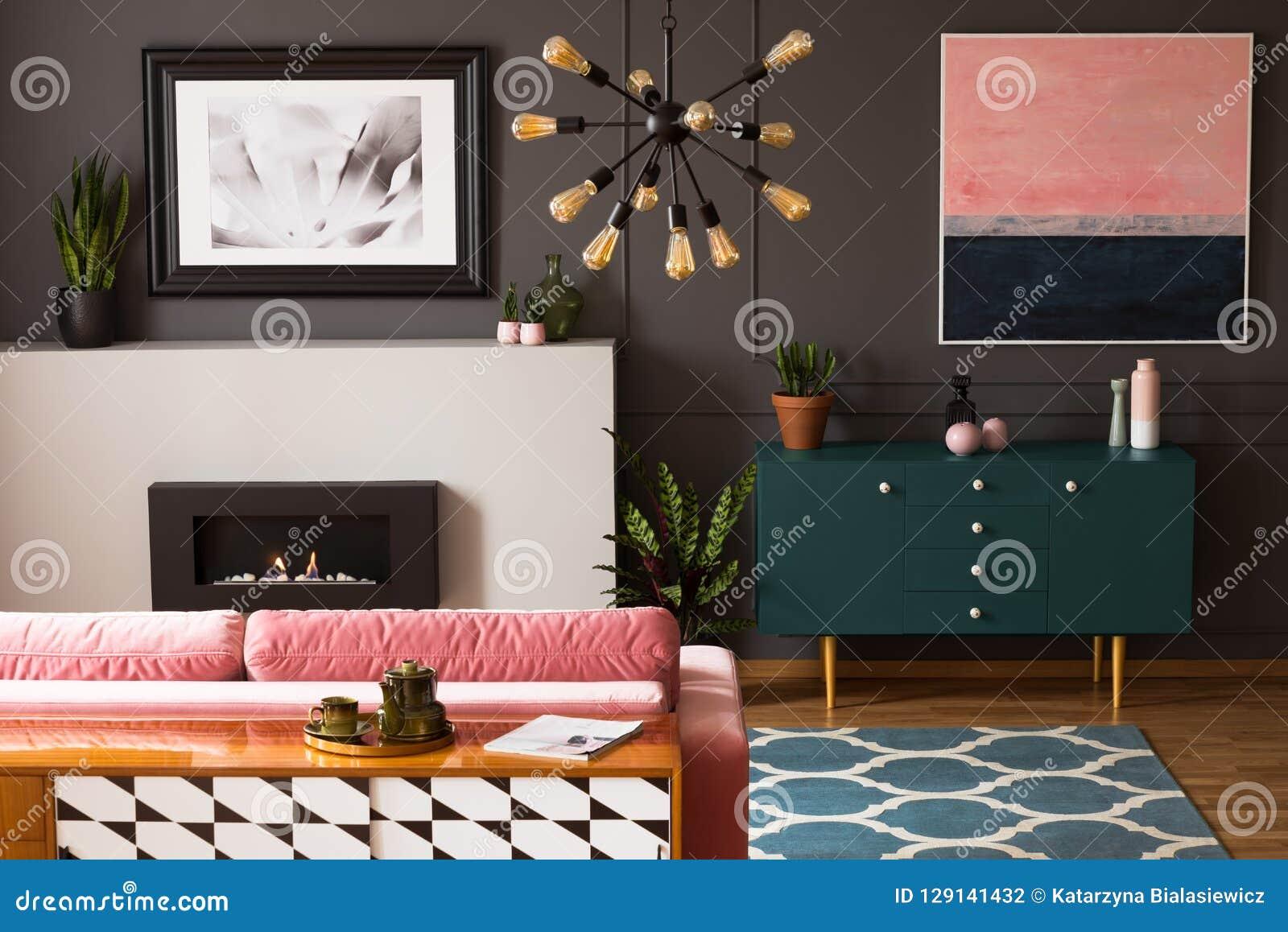 Pintura rosada sobre el gabinete verde en interior plano gris con la chimenea delante del sofá