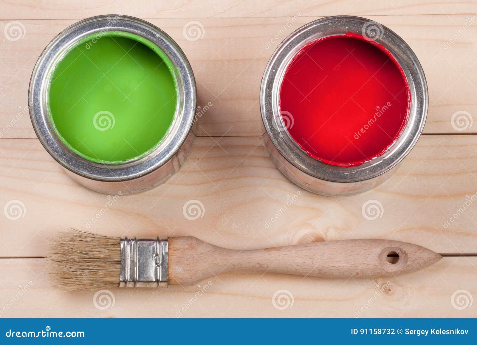 Pintura verde e vermelha no banco a reparar e escovar no fundo de madeira claro