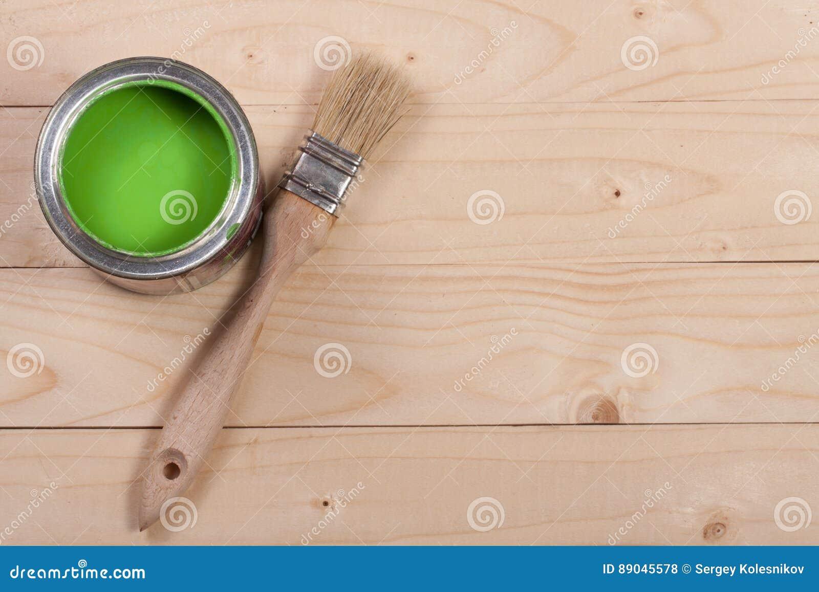 Pintura verde no banco a reparar e escovar no fundo de madeira claro com espaço da cópia para seu texto Vista superior