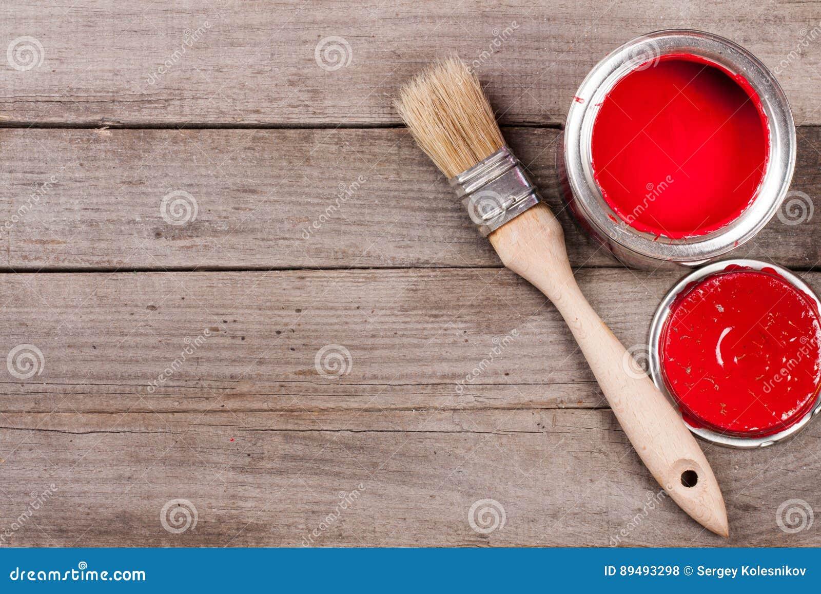 Pintura vermelha no banco a reparar e escovar no fundo de madeira velho com espaço da cópia para seu texto Vista superior