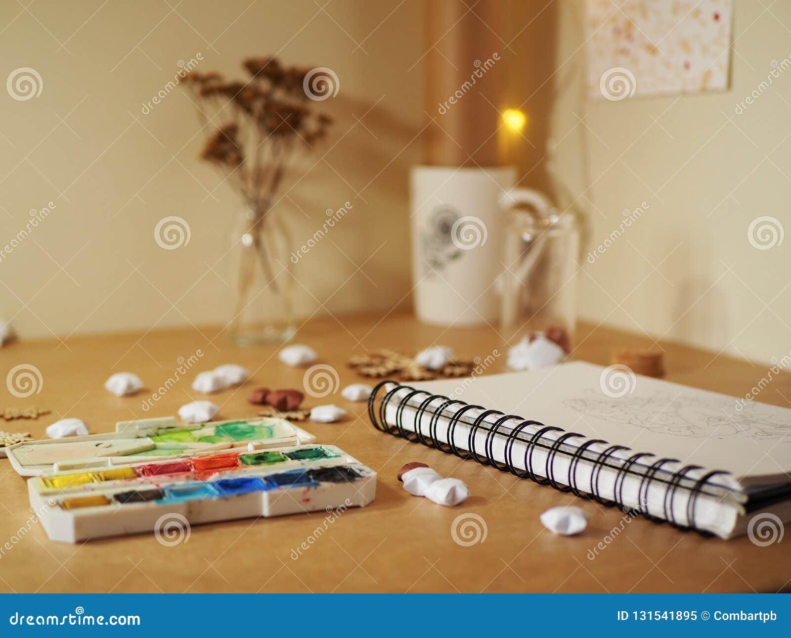Pinturas del cuaderno y del watercolour en un escritorio