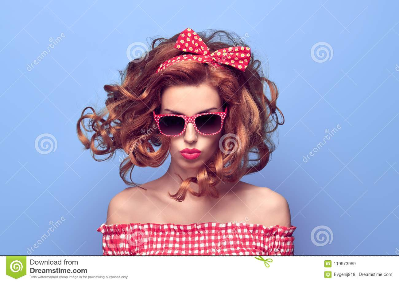 2980ad83489f PinUp Portrait Beauty Redhead Girl with Kiss Face Expression. Stylish Curly  hairstyle. Fashion Playful Woman in Pink Summer Bardot Dress