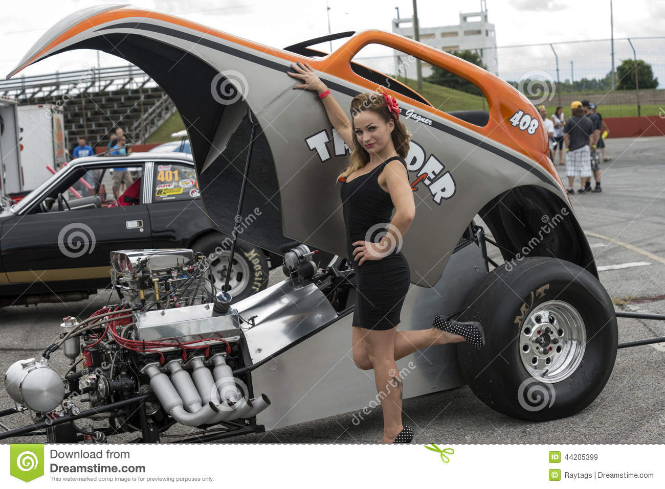 ... young woman pinup with a drag car at nostalgia drag racing event