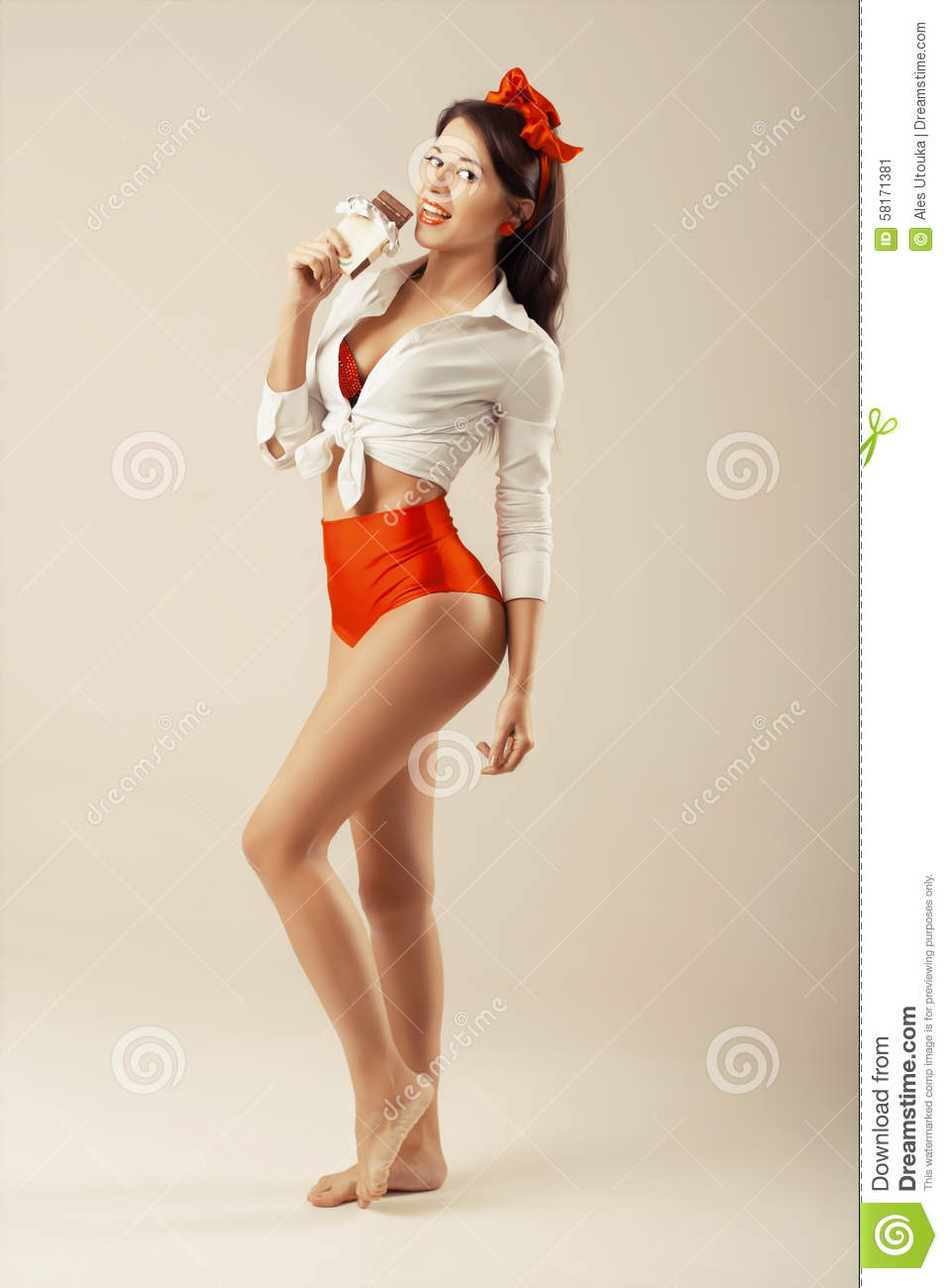 e3ffb8566b8 Pinup girl with chocolate stands in studio. Back to 1950s. retro style