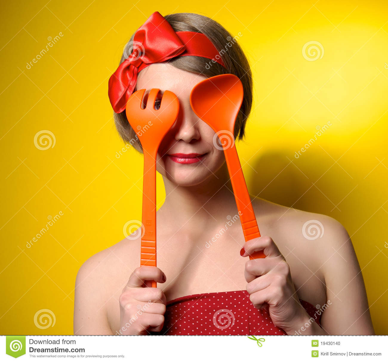 Pinup style housewife with kitchen utensils
